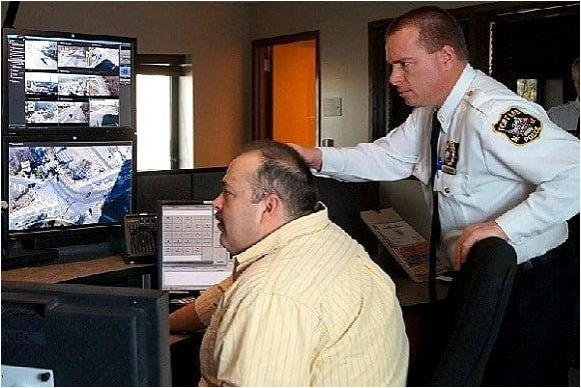 Police Officer Standing by Man on Computer