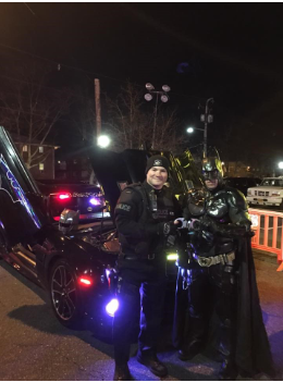 Police Officer Standing with Man in Batman Costume Next to Batmobile