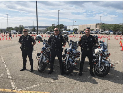 Three Police Officers Standing Next to Motorcycles
